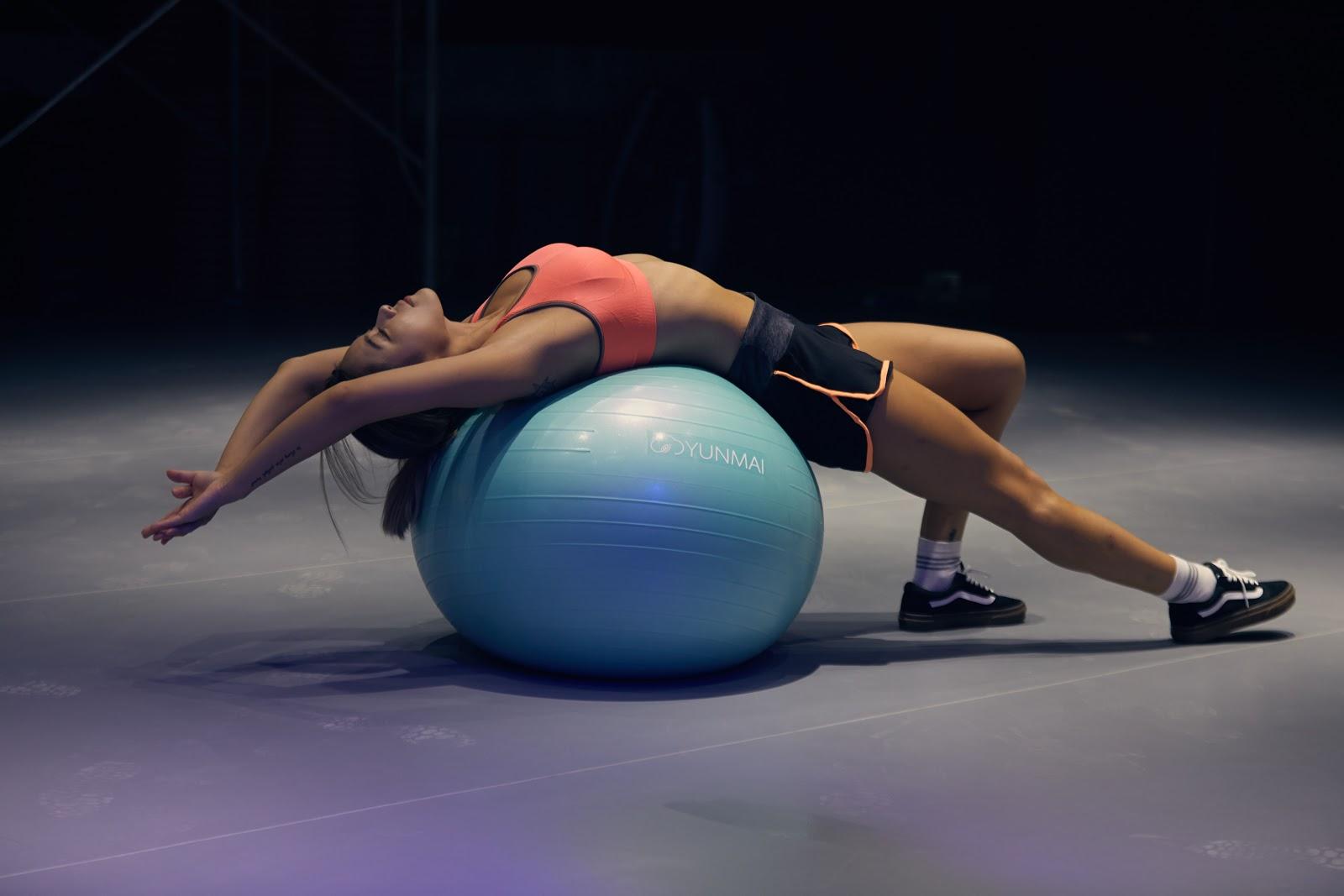 mulher fazendo exercícios com bola de yoga